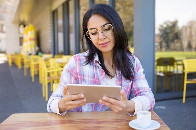 Zadowolona kobieta używa pastylkę i pijący kawę w kawiarni