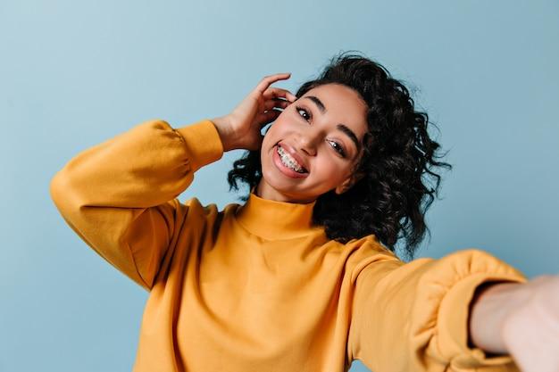 Zadowolona kobieta w aparatach ortodontycznych przy selfie