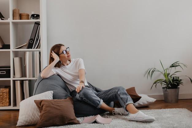 Zadowolona kobieta w dżinsach i t-shircie relaksowała się siedząc na krześle z torbą na półce z folderami.