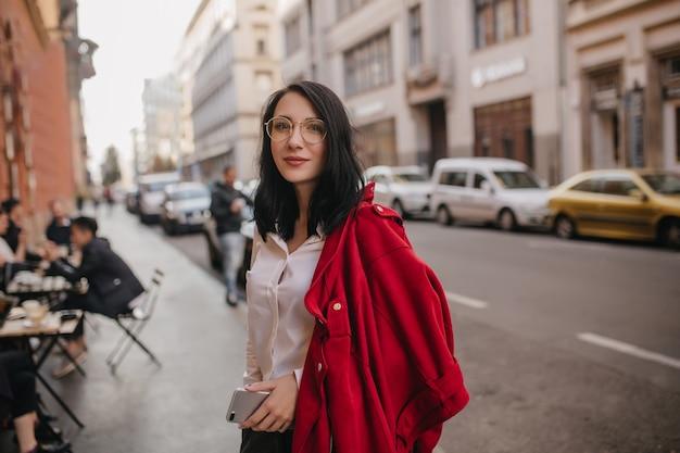 Zadowolona kobieta w okularach stojąc na ulicy z telefonem w ręku