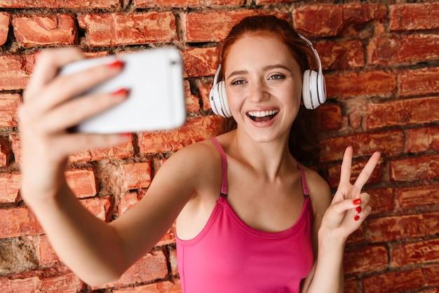 Zadowolona kobieta w słuchawkach robi zdjęcie selfie na telefonie komórkowym, jednocześnie wskazując znak pokoju na białym tle nad murem w pomieszczeniu