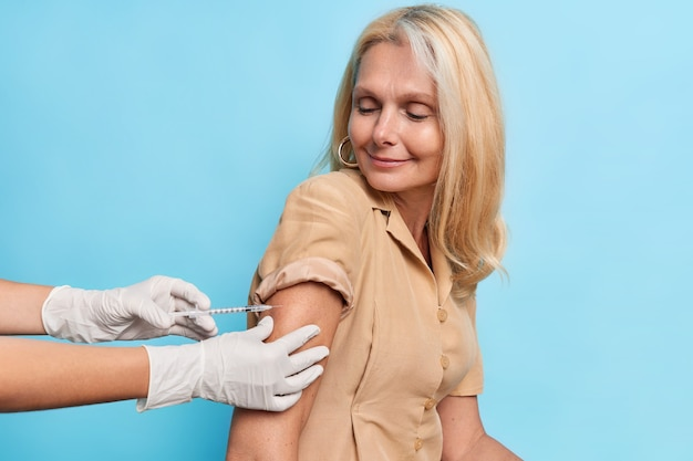 Zadowolona kobieta w średnim wieku czuje się chroniona po zaszczepieniu przeciwko koronawirusowi pozuje przed niebieską ścianą