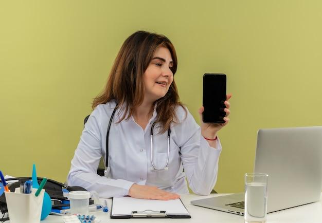 Zadowolona kobieta w średnim wieku ubrana w szlafrok medyczny i stetoskop siedząca przy biurku z narzędziami medycznymi i laptopem, trzymając i patrząc na telefon komórkowy na białym tle