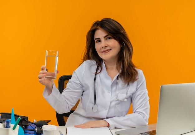 Zadowolona kobieta w średnim wieku ubrana w szlafrok medyczny i stetoskop siedząca przy biurku ze schowkiem na narzędzia medyczne i laptopem kładąca rękę na biurku trzymając szklankę wody na białym tle