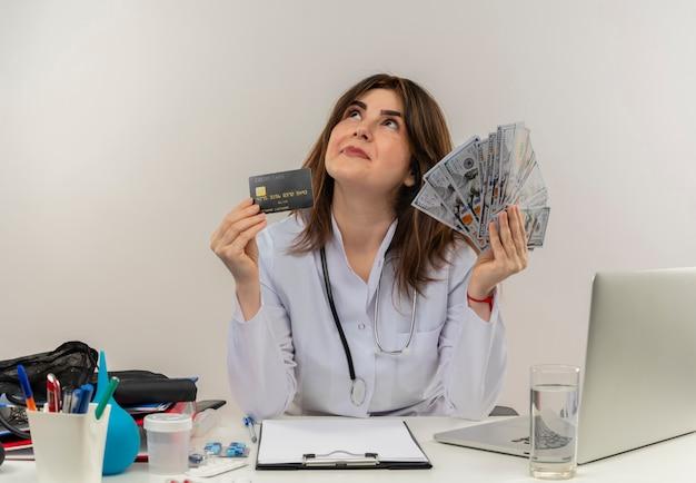 Zadowolona kobieta w średnim wieku ubrana w szlafrok medyczny i stetoskop siedząca przy biurku ze schowkiem na narzędzia medyczne i laptopem trzymająca kartę kredytową i pieniądze patrząc w górę na białym tle