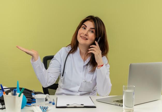 Zadowolona kobieta w średnim wieku ubrana w szlafrok medyczny ze stetoskopem siedząca przy biurku, pracująca na laptopie z narzędziami medycznymi, mówi przez telefon i wskazuje ręką na zieloną ścianę