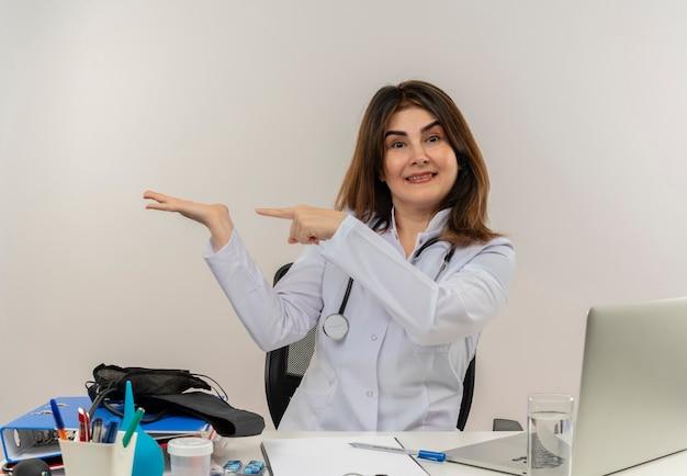 Zadowolona kobieta w średnim wieku ubrana w szlafrok medyczny ze stetoskopem siedząca przy biurku, pracująca na laptopie z narzędziami medycznymi, wskazująca palcem i ręką na bocznej białej ścianie
