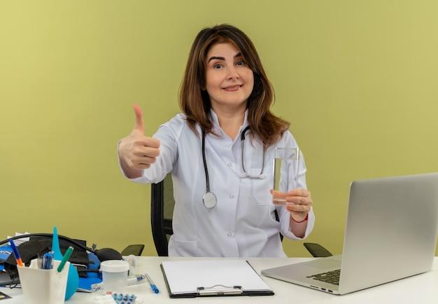 Zadowolona kobieta w średnim wieku ubrana w szlafrok medyczny ze stetoskopem siedząca przy biurku pracuje na laptopie z narzędziami medycznymi trzymając szklankę wody z kciukiem do góry na zielonej ścianie z miejscem na kopię