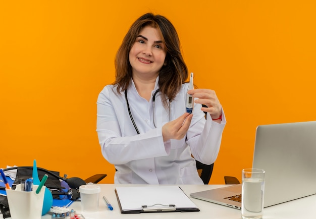 Zadowolona kobieta w średnim wieku ubrana w szlafrok medyczny ze stetoskopem siedząca przy biurku pracuje na laptopie z narzędziami medycznymi trzymającymi termometr na odizolowanej pomarańczowej ścianie z miejscem na kopię