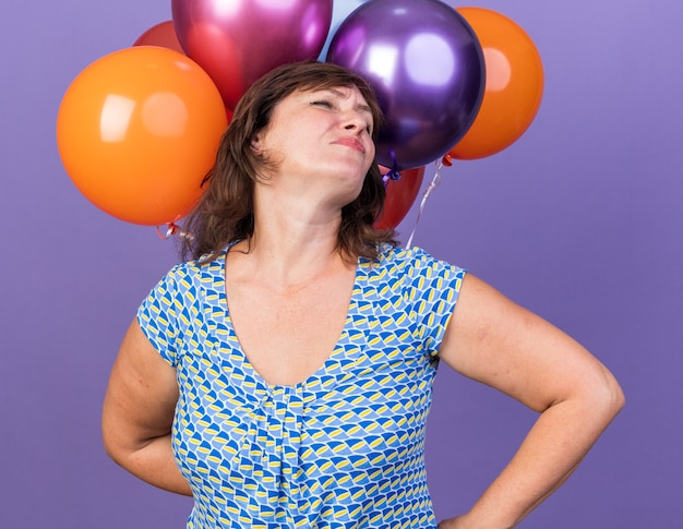 Zadowolona kobieta w średnim wieku z wiązką kolorowych balonów uśmiechnięta pewnie świętująca przyjęcie urodzinowe stojąca nad fioletową ścianą