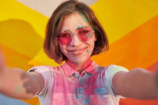 Zadowolona kobieta w stylowych okularach przeciwsłonecznych iz farbą na twarzy