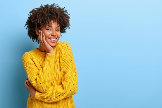 Zadowolona kobieta z afro pozuje w różowym swetrze