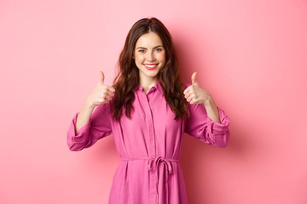 Zadowolona kobieta z aprobatą pokazująca kciuki do góry, powiedz tak, zgódź się i zatwierdź wybór, chwaląc cię, stojąc pod różową ścianą.