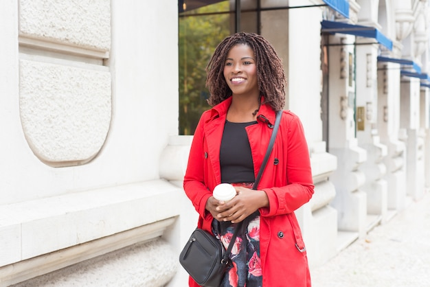 Zadowolona kobieta z kawą iść na ulicę