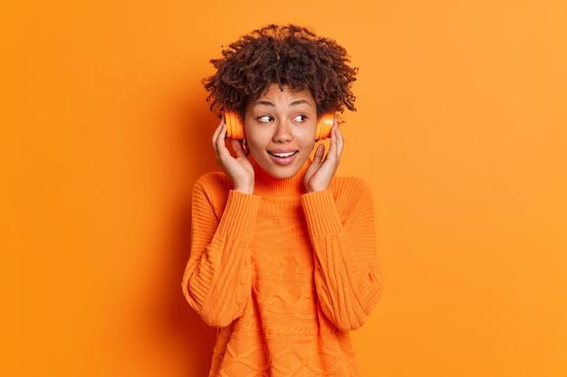 Zadowolona kobieta z kręconymi włosami słucha ścieżki dźwiękowej przez słuchawki, patrzy na bok, uśmiecha się przyjemnie, nosi swobodny sweter odizolowany na pomarańczowej ścianie