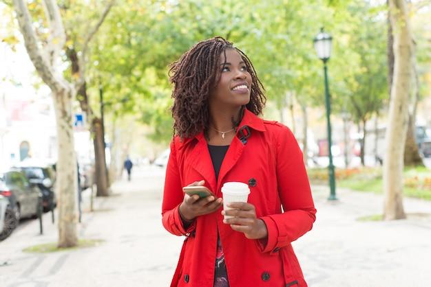 Zadowolona kobieta z smartphone i papierową filiżanką