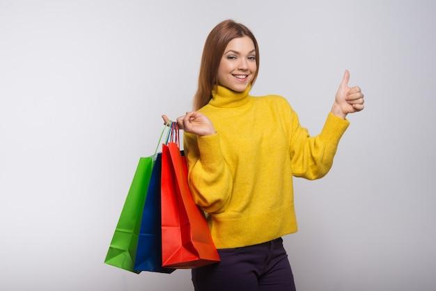Zadowolona kobieta z torba na zakupy pokazuje kciuk up