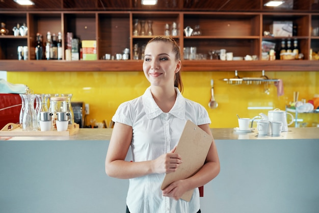Zadowolona kobieta zarządza sklep z kawą ze schowkiem