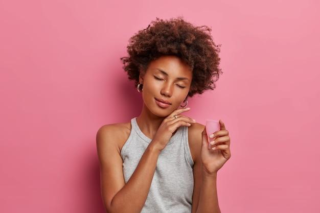 Zadowolona, kręcona kobieta z przyjemnością dotyka twarzy, stoi z zamkniętymi oczami, trzyma elastyczną miseczkę menstruacyjną do włożenia do pochwy podczas miesiączki, chroni przed wyciekiem krwi, izolowana na różowej ścianie