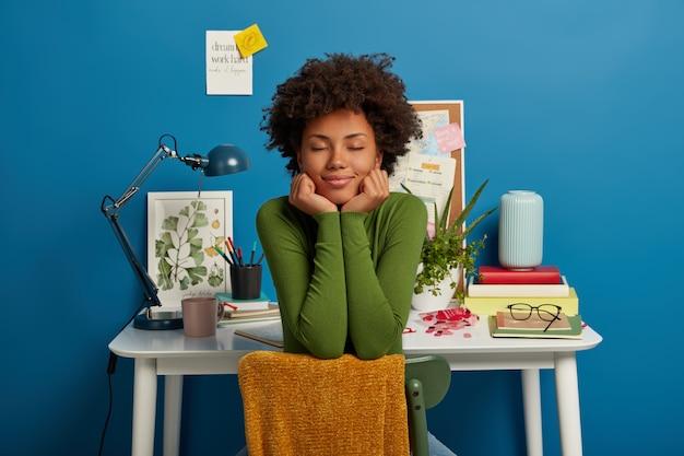 Zadowolona, kręcona nauczycielka pracuje nad planem strategicznym, siedzi na wygodnym krześle, trzyma ręce pod brodą, przykleja notatki z pisemnymi zadaniami, pozuje w miejscu pracy