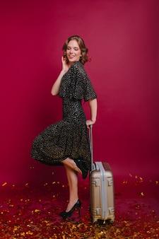 Zadowolona krótkowłosa kobieta stojąca na jednej nodze z walizką i uśmiechnięta z zamkniętymi oczami