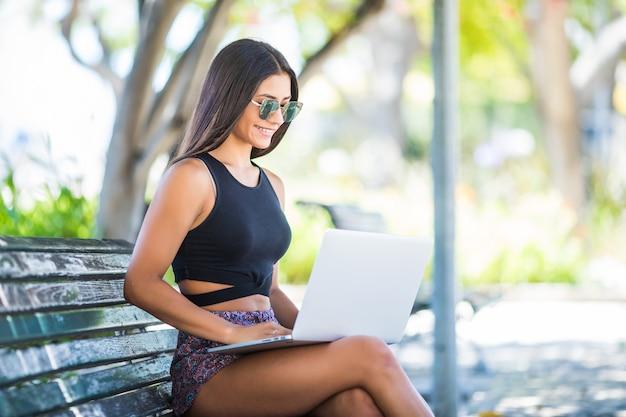 Zadowolona łacińska kobieta siedzi na ławce w parku i przy użyciu komputera przenośnego