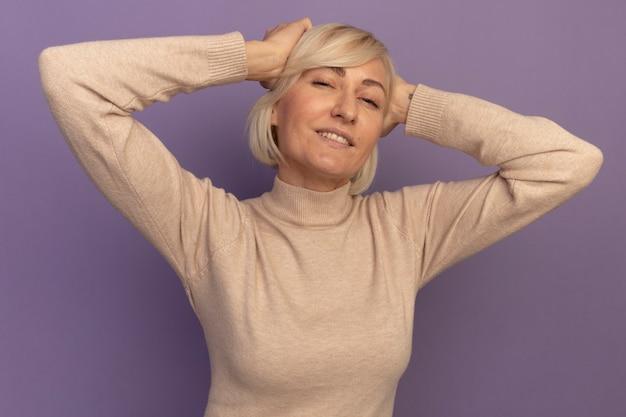 Zadowolona ładna blondynka słowiańska kobieta kładzie ręce na głowie na fioletowo