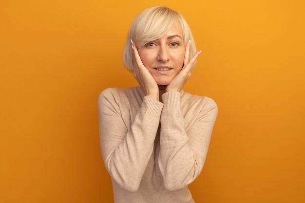 Zadowolona ładna blondynka słowiańska kobieta kładzie ręce na twarzy odizolowanej na pomarańczowej ścianie