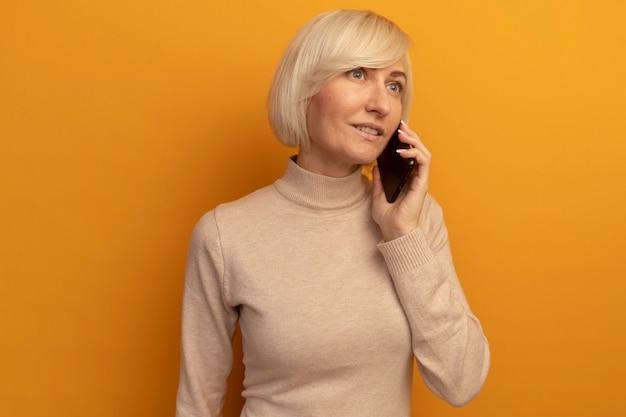 Zadowolona ładna blondynka słowiańska kobieta rozmawia przez telefon, patrząc na bok na białym tle