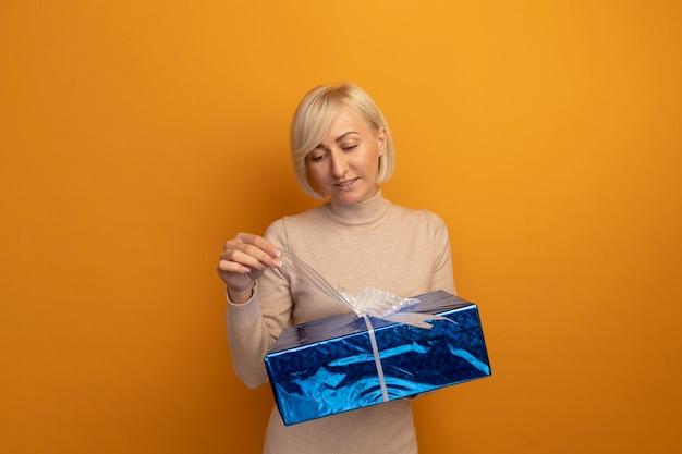 Zadowolona ładna blondynka słowiańska kobieta trzyma i patrzy na pudełko na białym tle na pomarańczowej ścianie