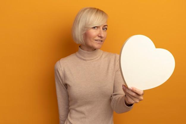 Zadowolona ładna blondynka słowiańska kobieta trzyma kształt serca patrząc z przodu na białym tle na pomarańczowej ścianie