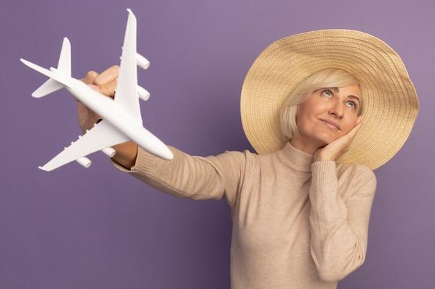 Zadowolona ładna blondynka słowiańska kobieta w kapeluszu plażowym kładzie rękę na twarzy trzyma model samolotu patrząc na fioletowo