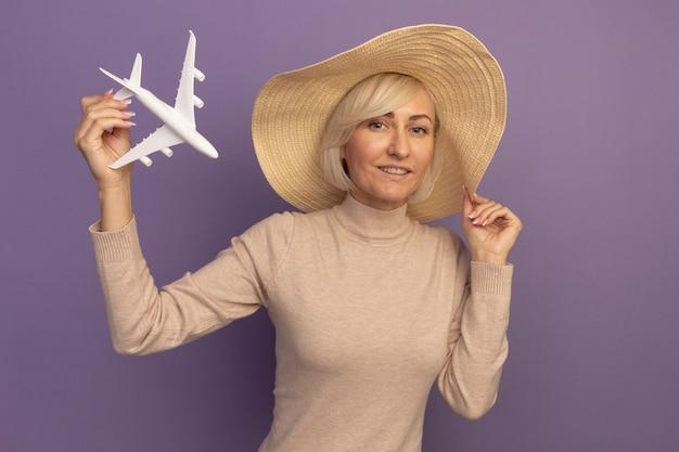 Zadowolona ładna blondynka słowiańska kobieta z kapeluszem plażowym, trzymając model samolotu na fioletowo