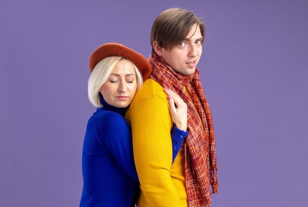 Zadowolona ładna blondynka z beretem przytula przystojnego słowiańskiego mężczyznę z szalikiem na szyi na izolowanej fioletowej ścianie z kopią przestrzeni