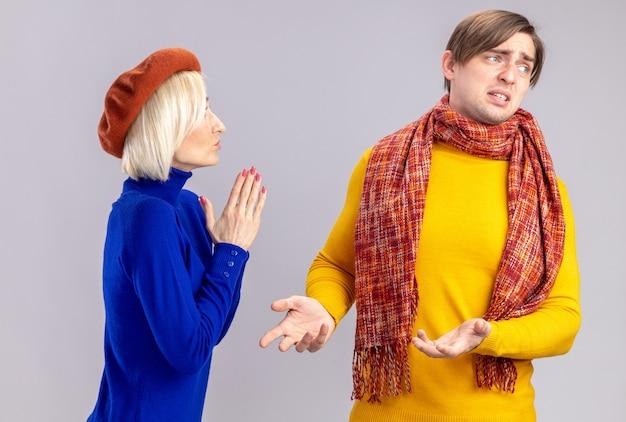 Zadowolona ładna blondynka z beretem trzymająca się za ręce i patrząca na niezadowolonego przystojnego słowiańskiego mężczyznę z szalikiem na szyi na białym tle na białej ścianie z kopią przestrzeni