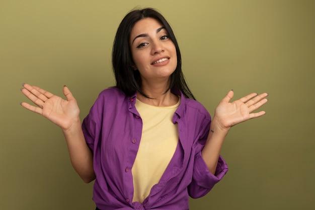 Zadowolona ładna brunetka kobieta trzyma ręce otwarte na białym tle na oliwkowej ścianie