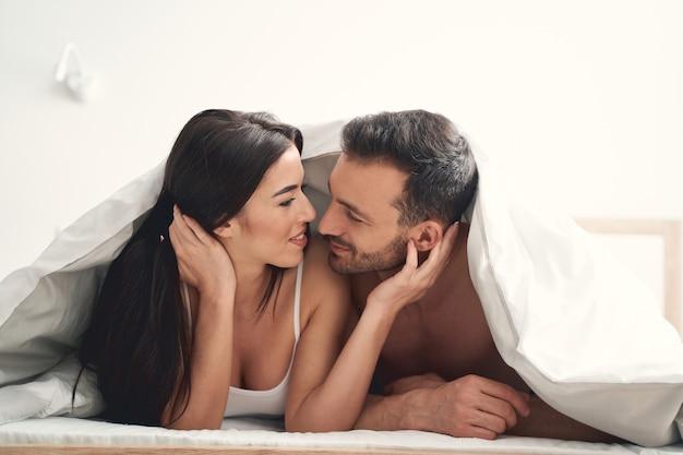 Zadowolona ładna ciemnowłosa kobieta i jej przystojny młody mąż uśmiechają się do siebie w łóżku