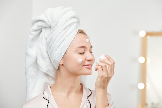 Zadowolona ładna dziewczyna ciesząca się zapachem kremu do twarzy, dbając o poranku o swoją twarz i ciało