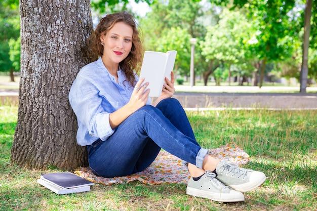 Zadowolona ładna dziewczyna czyta podręcznika w parku