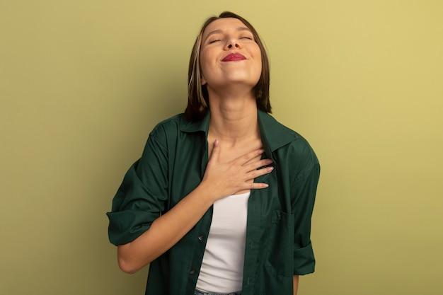 Zadowolona ładna kaukaska kobieta kładzie rękę na piersi na oliwkowej zieleni