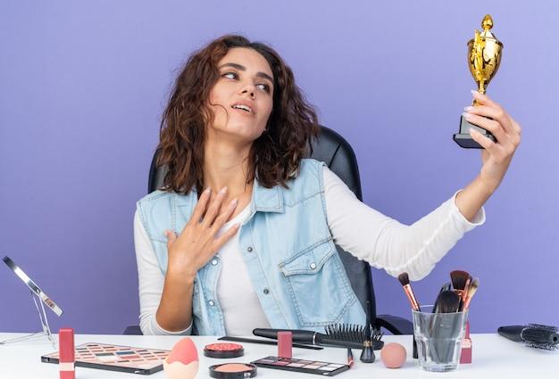 Zadowolona ładna kaukaska kobieta siedzi przy stole z narzędziami do makijażu, trzymając i patrząc na puchar zwycięzcy i kładąc dłoń na jej klatce piersiowej