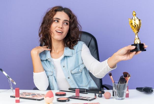 Zadowolona ładna kaukaska kobieta siedzi przy stole z narzędziami do makijażu, trzymając i patrząc na puchar zwycięzcy odizolowaną na fioletowej ścianie z miejscem na kopię
