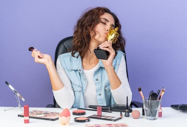 Zadowolona ładna kaukaska kobieta siedzi przy stole z narzędziami do makijażu, trzymając pędzel do makijażu i całując puchar zwycięzcy na fioletowej ścianie z miejsca na kopię