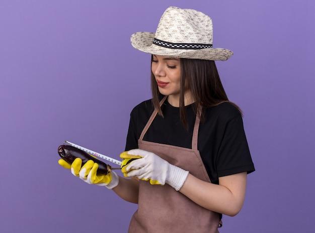 Zadowolona ładna kaukaska ogrodniczka w kapeluszu ogrodniczym i rękawiczkach mierząca bakłażana za pomocą taśmy mierniczej