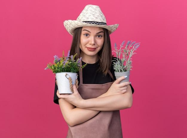 Zadowolona ładna kaukaska ogrodniczka w kapeluszu ogrodniczym stoi ze skrzyżowanymi rękami trzymając doniczki izolowane na różowej ścianie z kopią przestrzeni