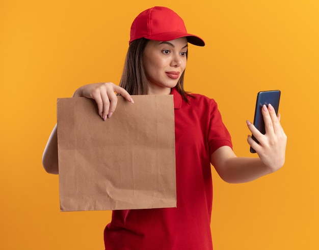 Zadowolona ładna kobieta doręczycielska w mundurze trzyma papierową paczkę i patrzy na telefon odizolowany na pomarańczowej ścianie z miejscem na kopię