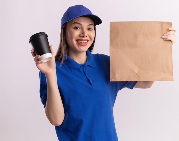 Zadowolona ładna kobieta dostarczająca w mundurze trzymająca papierową paczkę i papierowy kubek na białej ścianie z miejscem na kopię