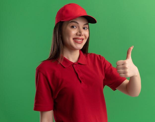 Zadowolona ładna kobieta dostawy w mundurze kciuki do góry na zielono