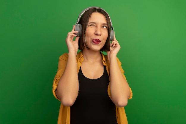 Zadowolona ładna kobieta na słuchawkach wystawia język i patrzy na bok odizolowany na zielonej ścianie