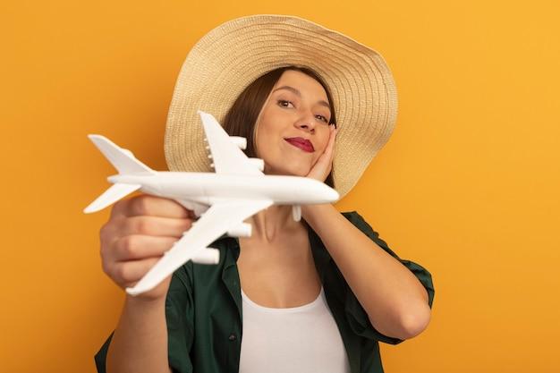 Zadowolona ładna kobieta w kapeluszu plażowym kładzie rękę na twarzy i trzyma model samolotu na pomarańczowej ścianie